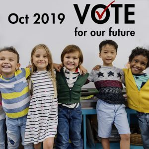 A group of children with a white board above them and the following text: October 2019 Vote for our future